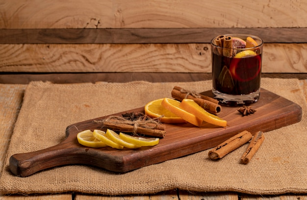 Sliced lemon and orange with a glass of glintwine, cinnamon sticks and anise.