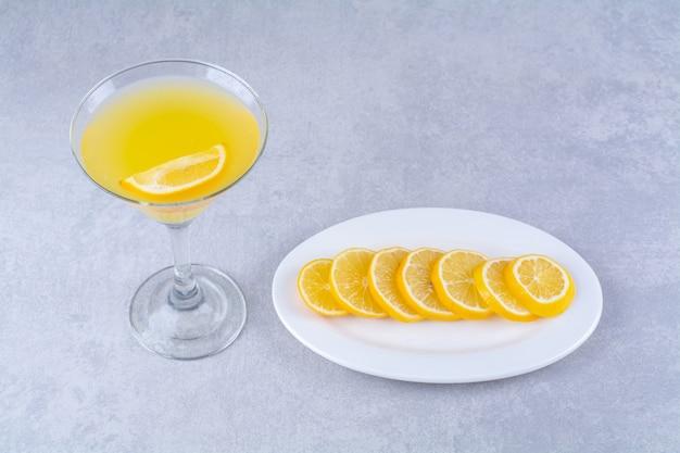 Fette di limone su un piatto accanto a un bicchiere di succo d'arancia, sul tavolo di marmo.