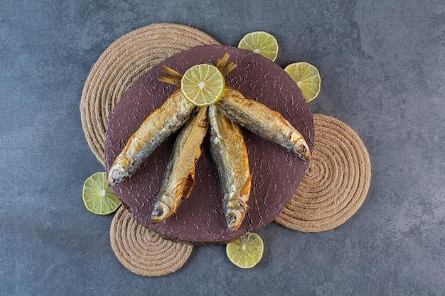 大理石の表面にあるトリベットのボードにスライスしたレモンと乾燥した塩漬けの魚