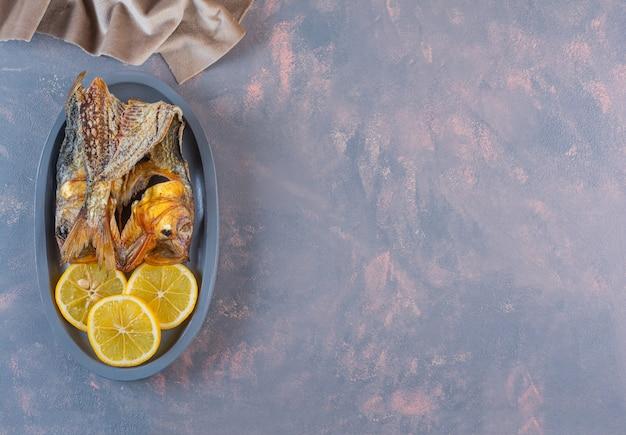 대리석 표면에 나무 접시에 레몬 슬라이스와 말린 소금에 절인 생선