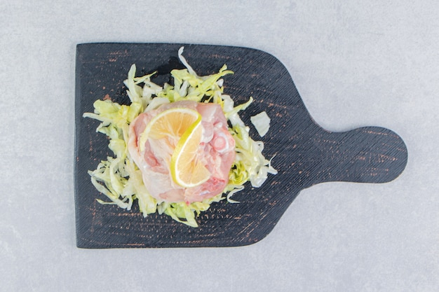 スライスしたレモンとグリーン、肉をボードに、白い表面に