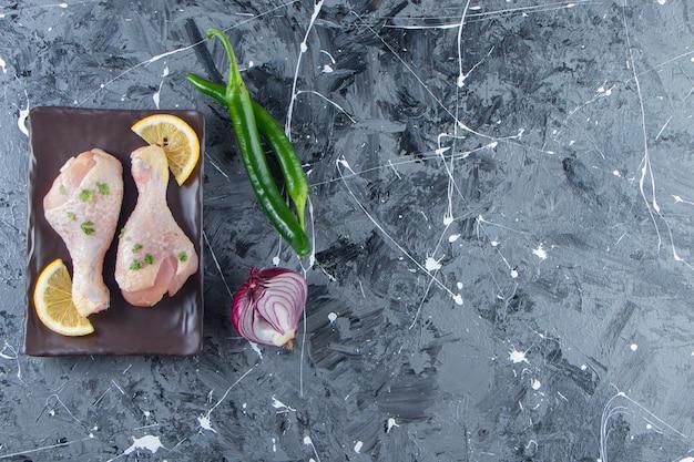 Sliced lemons and drumsticks on a platter next to vegetables , on the marble background.