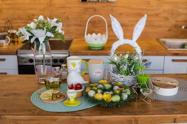 Нарезанные лимоны, оливки, миндаль на деревянной доске, пасхальные яйца на большом семейном столе