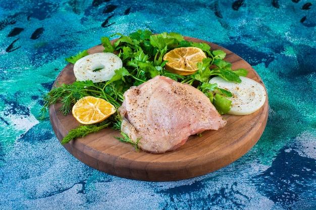 Нарезанные лимоны, лук и петрушка с куриным мясом на доске