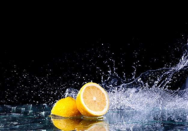 Sliced lemons in the water on black surface