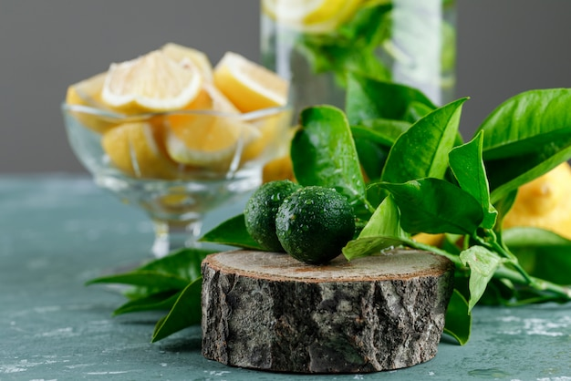 Sliced lemons with leaves, detox water, wooden board in a vase on plaster and grey surface
