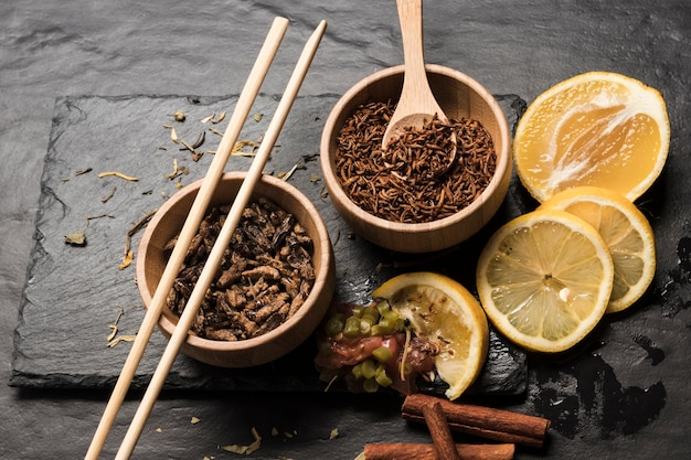 Sliced lemons with wooden bowls filled with insects