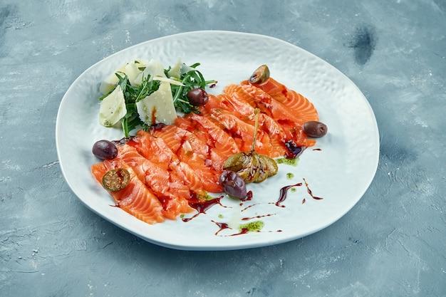 ルッコラとパルメザンチーズの塩漬けサーモンをスライスしました。ケッパーとオリーブの白い皿に赤い魚の刺身。新鮮な魚介類