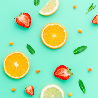Sliced lime orange strawberry sea ​​buckthorn and green leaves