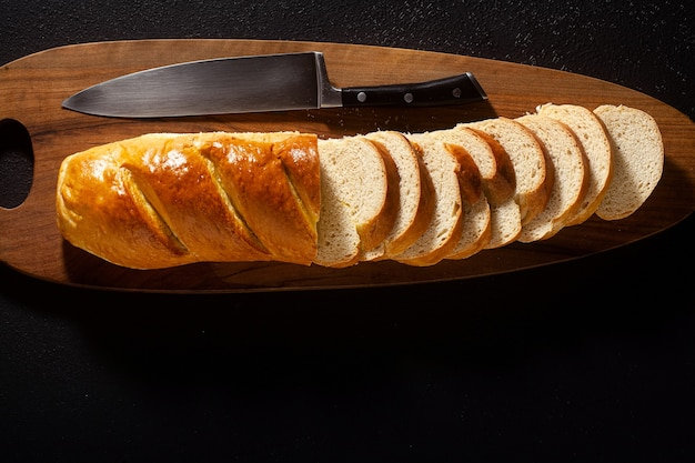 Sliced loaf of bread on a chopping board and a chef's knife on a black