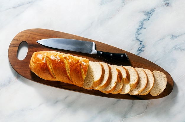 Sliced loaf of bread on a cutting board and a chef's knife on a marble table