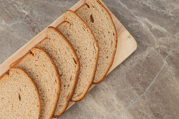 A sliced loaf of brown bread on a stone surface