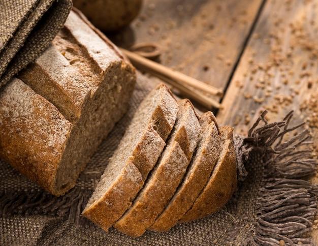 パン粉が付いている木の表面の布ナプキンのパンのスライスされた一斤