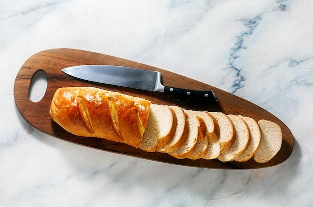 まな板の上にパンをスライスし、大理石のテーブルの上にシェフのナイフ