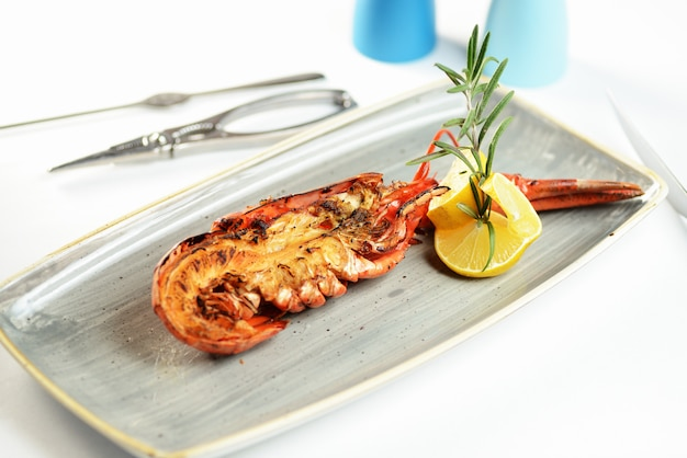 Sliced lobster on a plate with lemon. lobster tongs