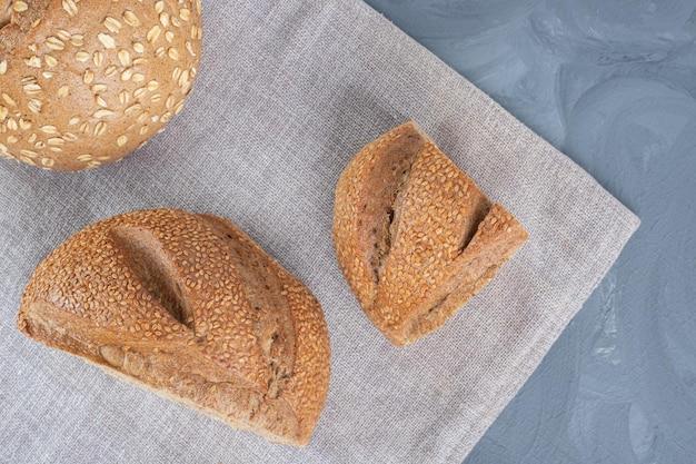 大理石のテーブルのタオルの上にゴマをコーティングしたスライスしたパンの塊。