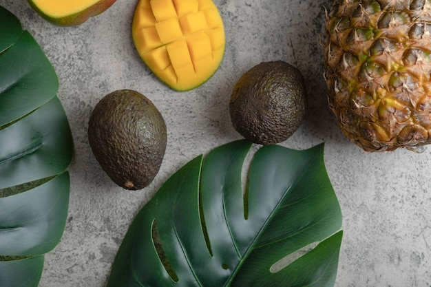 Sliced mango, coconut, pineapple and ripe avocados on marble surface.