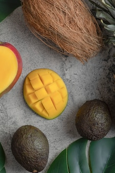 Sliced mango, coconut and ripe avocado fruits on marble surface.