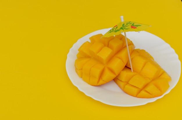 Нарезанное манго подается в белой тарелке на красочном фоне