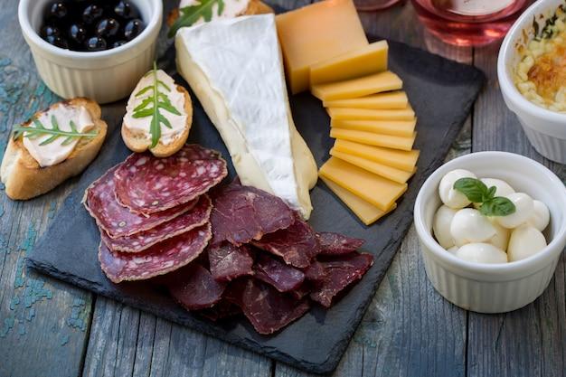 Нарезанное мясо и сыр на доске