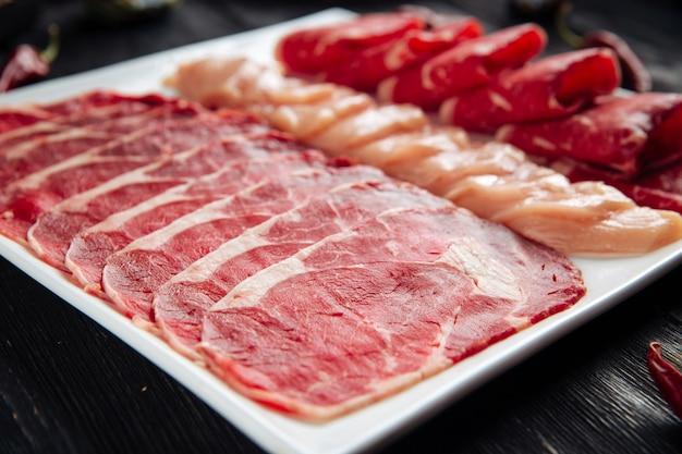 Нарезанное мясное ассорти на белой квадратной тарелке