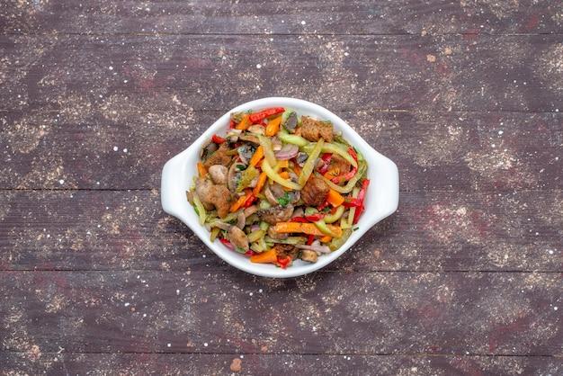 Piatto di carne a fette con verdure cotte all'interno del piatto su carne di verdure farina di legno marrone, cibo