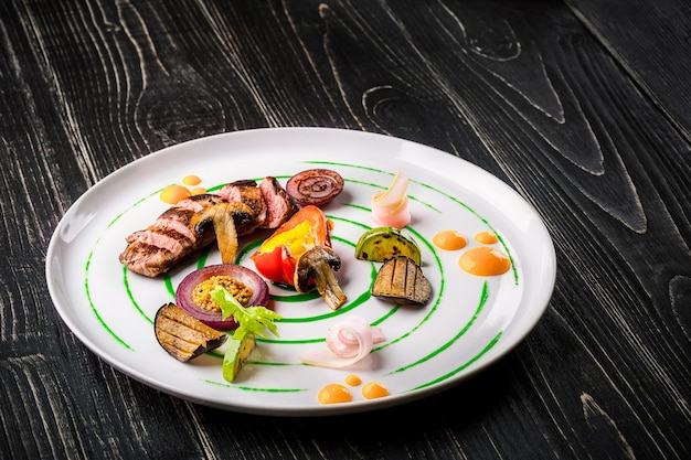 Sliced meat with fresh herbs vegetables and spices on a white plate on a black wooden background top...