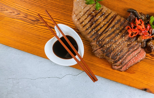 Sliced medium rare grilled beef with soy sauce on cutting board.
