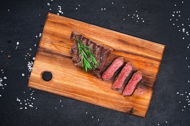 Sliced medium rare grilled steak on cutting board with rosemary and spices