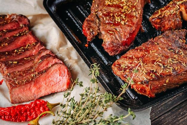 Sliced medium rare grilled steak on paper for baking, close up