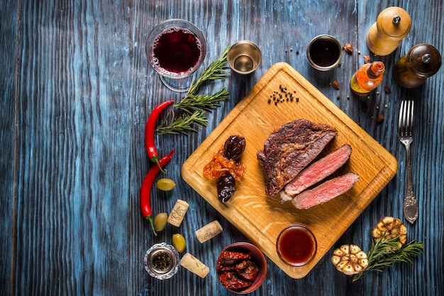 Sliced medium rare grilled steak on rustic wooden background with rosemary and spices