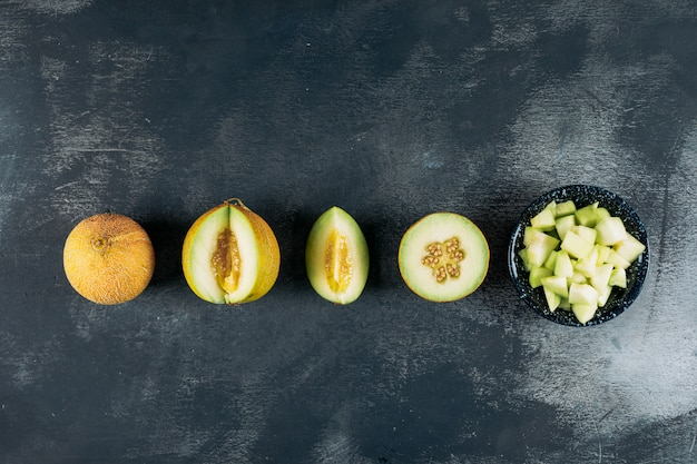 Sliced melons with melon in a black bowl top view on a dark wooden background copy space for text