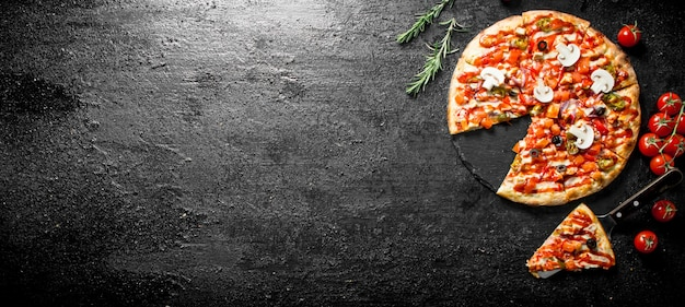 Sliced mexican pizza with cherry tomatoes and rosemary.