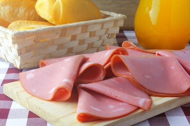 Нарезанная мортаделла на разделочной доске на кухне с деревенским столом