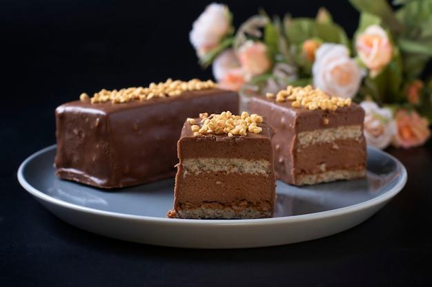 헤이즐넛 프랄린, 밀크 초콜릿 및 덮힌 고급 초콜릿 너트 글레이즈로 무스 디저트 슬라이스