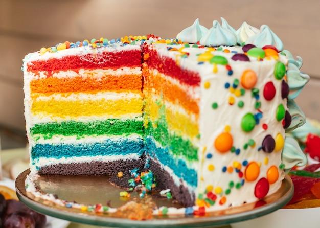 Нарезанный разноцветный радужный торт. торт со слоями ярких цветов внутри