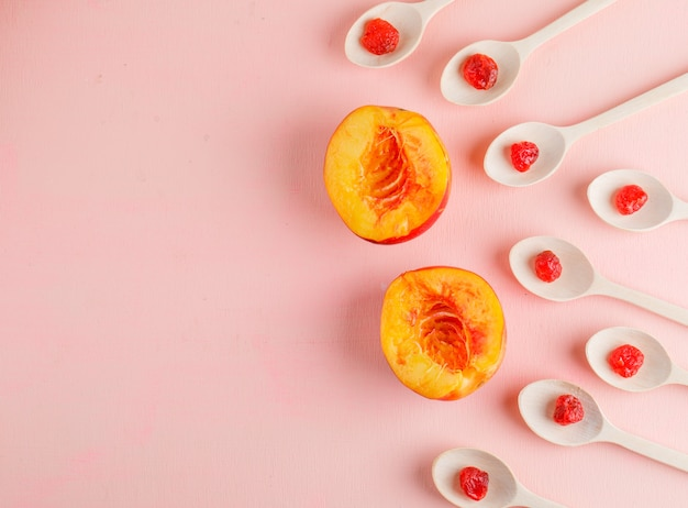 Sliced nectarine with dried cherry on pink table, flat lay.