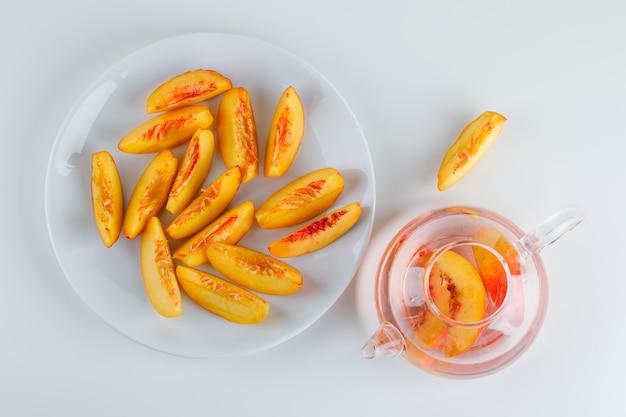 Нарезанный нектарин с напитком в тарелку на белом столе, плоский лежал.