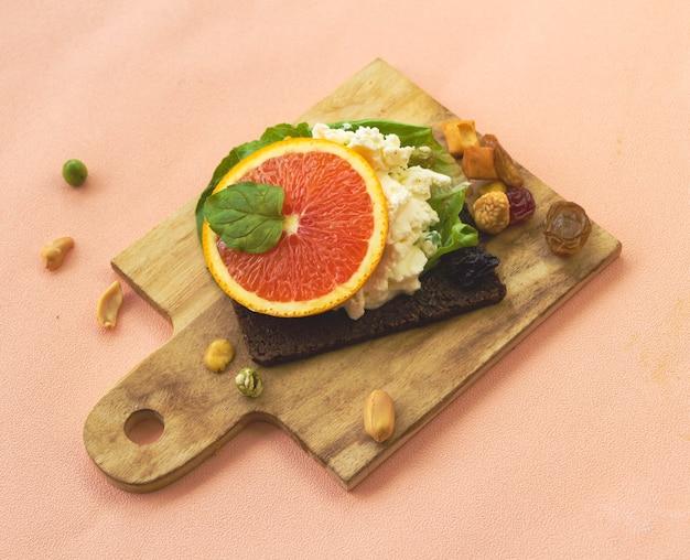 Ломтик апельсина положить на сливочный сыр и мультизерновой хлеб, на деревянный поднос, домашняя закуска. фруктовые канапе