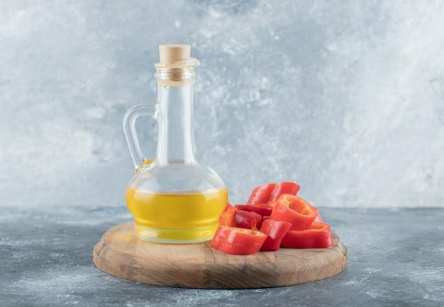Ломтик сладкого болгарского красного перца со стеклянной бутылкой масла на деревянной доске.