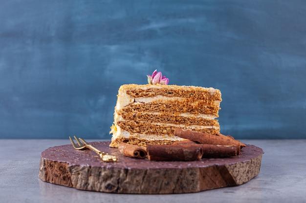 Ломтик сладкого медового торта с палочками корицы на каменной поверхности.