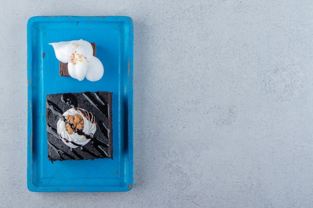 블루 접시에 크림과 함께 맛 있는 초콜릿 브라 우니의 슬라이스. 고품질 사진