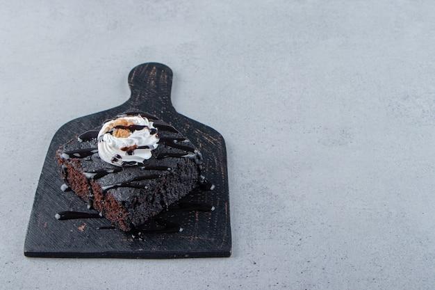 커팅 보드에 크림과 함께 맛있는 초콜릿 브라우니 조각. 고품질 사진