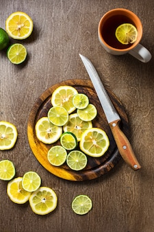 レモン、ライムスレート、木製のカウンタートップの背景にスライス