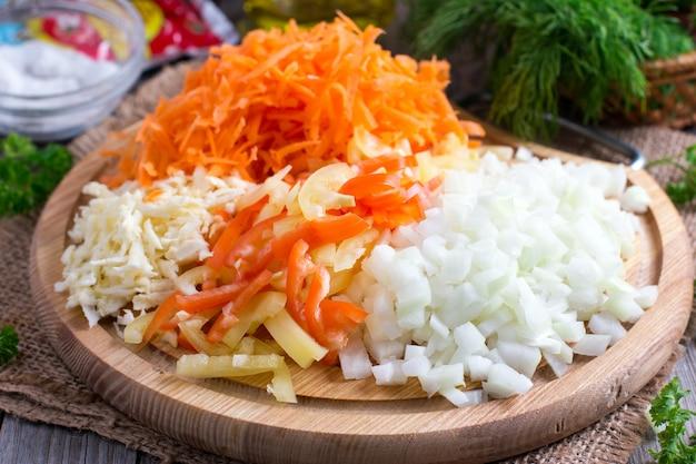 Нарезанный лук, морковь, болгарский перец на разделочной доске