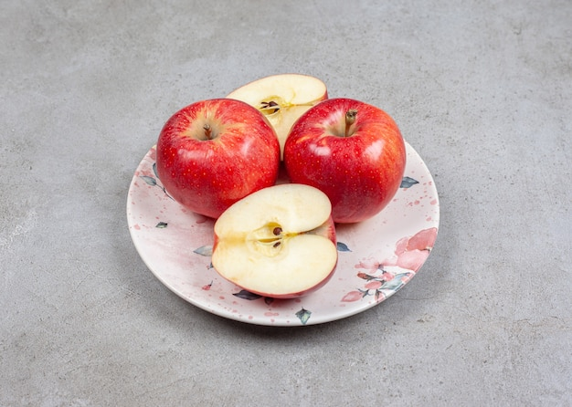 접시에 슬라이스 또는 전체 사과. 신선한 사과 사진을 닫습니다.