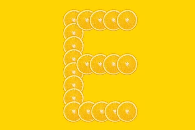 Нарезанный оранжевый алфавит - буква e. желтый фон. свежие здоровые апельсиновые плоды. сочный шрифт.