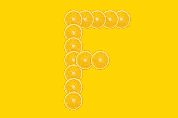 Нарезанный оранжевый алфавит - буква f. желтый фон. свежие здоровые апельсиновые плоды. сочный шрифт.