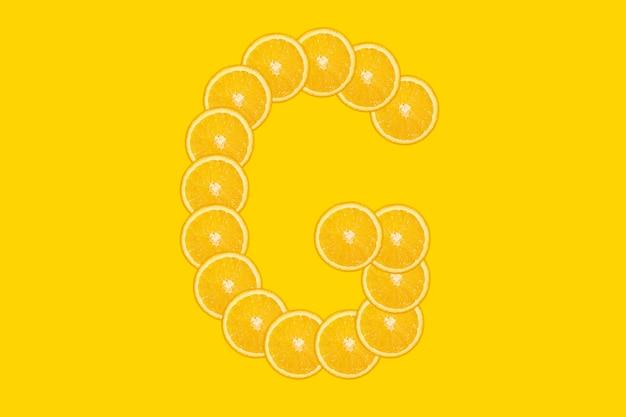 Нарезанный оранжевый алфавит - буква g. желтый фон. свежие здоровые апельсиновые плоды. сочный шрифт.