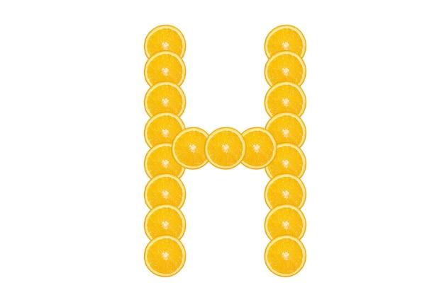 Нарезанный оранжевый алфавит - буква h. изолированный белый фон. свежие здоровые апельсиновые плоды. сочный шрифт.